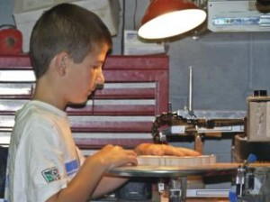 Isaiah cuts a project on the Hawk G4 scroll saw he bought with his own money.