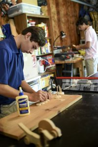 Sam Leppo '17 assembles parts for the handmade toys he and his brother Logan cut and sanded.